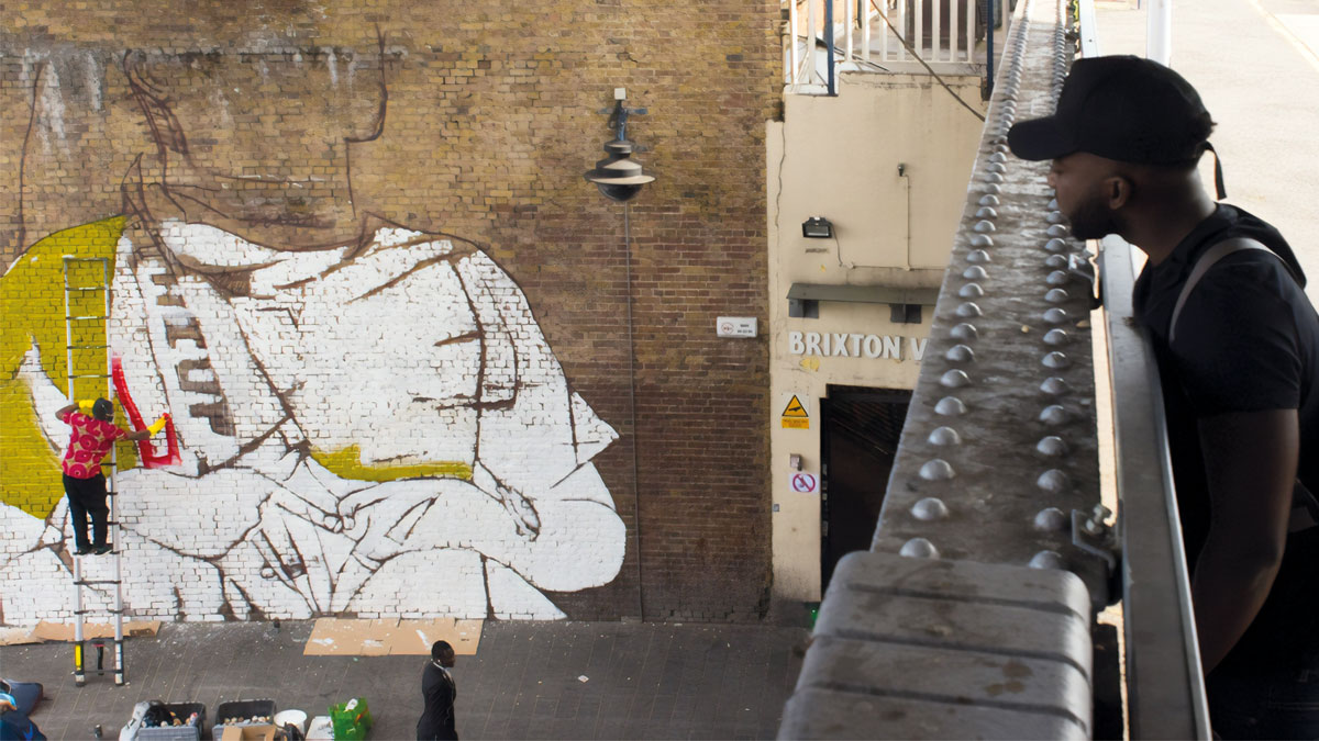 Man looking over bridge at artwork being painted on the wall, Brixton design trail © Luke Forsythe